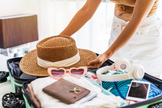 Young woman traveler sitting on the bed packing her suitcase preparing for travel on summer vacation