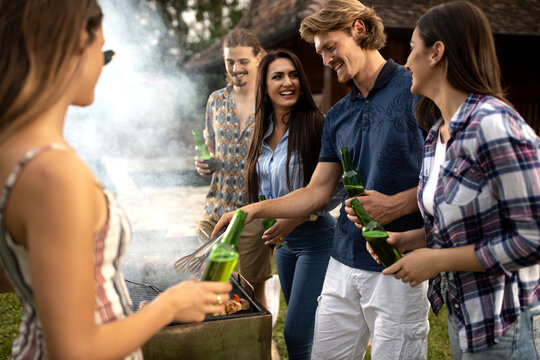 Group of casual people enjoying themselves outdoors while preparing a bbq
