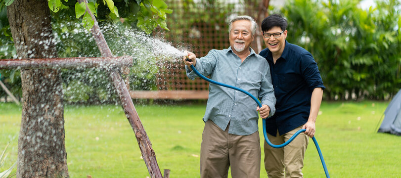 Elderly Asian father and Adult son Happy family in backyard watering plant with hose.