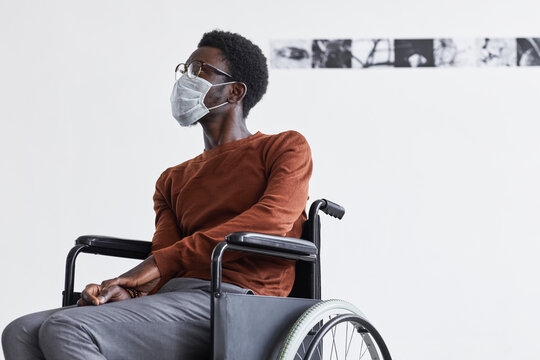 Minimal portrait of African-American man using wheelchair and wearing mask while looking at paintings in modern art gallery, copy space