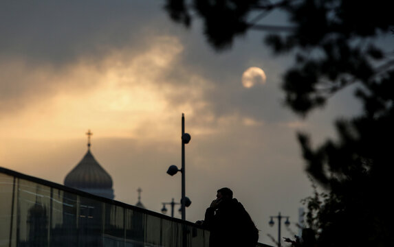 A man speaks on the phone during sunset in Moscow