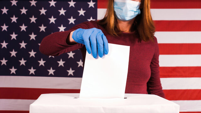 Woman voting with gloves and face mask at coronavirus pandemic. 2020 United States presidential election.