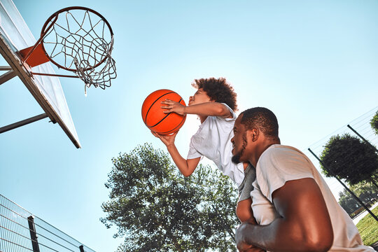 Afro-American kid playing basketball with his father