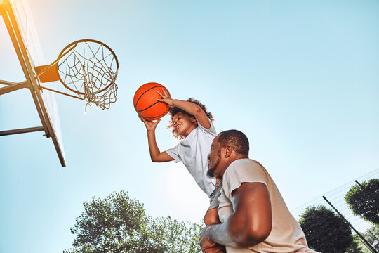 Joyful child playing basketball with his caring father