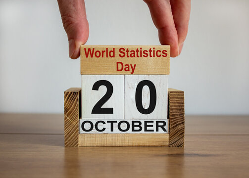 Male hand puts a block with the inscription 'World Statistics Day' on cubes with the date october 20. Wooden table. Beautiful white background, copy space.