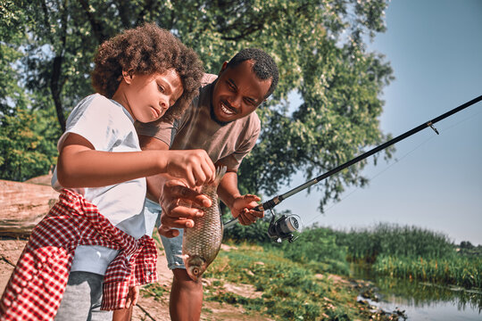 Cute Afro-American child holding a fish he just caught