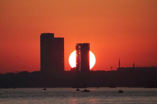 The sun sets behind the skyscraper in Zeytinburnu district in Istanbul