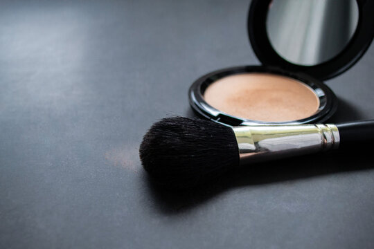 Close-up of a black makeup brush with flesh-colored powder at the end. On the background of an open box with pink powder. Dark, almost black background. Copy space