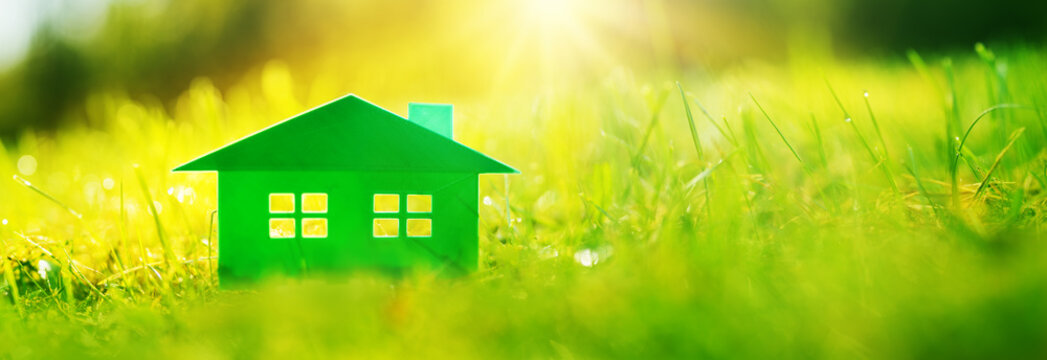 Green house on the fresh grass on a sunny day.