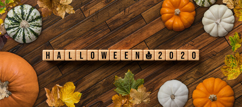 autumn decoration with pumpkins and colorful leaves and message HALLOWEEN 2020 on wooden background
