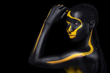 Face art. Woman with black and yellow body paint. Young african girl with colorful bodypaint. An amazing model with yellow makeup. Closeup face.