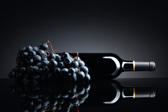 Bottle of red wine and a bunch of grapes on a black reflective background.