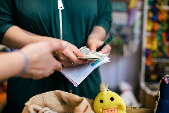 Shop Owner Counting Out Money After Buying Toys