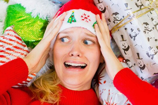 A woman worried and stressed out during the holiday season. Christmas gift shopping.