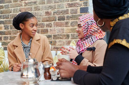 Smiling Muslim women having coffee
