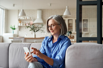 Fototapeta Relaxed mature old 60s woman, older middle aged female customer holding smartphone using mobile app, texting message, search ecommerce offers on cell phone technology device sitting on couch at home. obraz