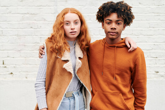 Two diverse teens standing outside