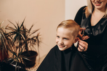 Obraz Eight-year-old blonde boy at the barbershop. A hairdresser cuts a haircut at a home beauty salon. Selective focus. - fototapety do salonu