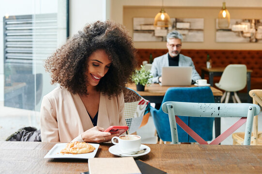 Smiling businesswoman texting in a cafe