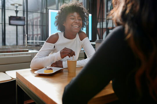 Two friends laughing in a cafe