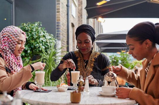 Three Muslim women having coffee