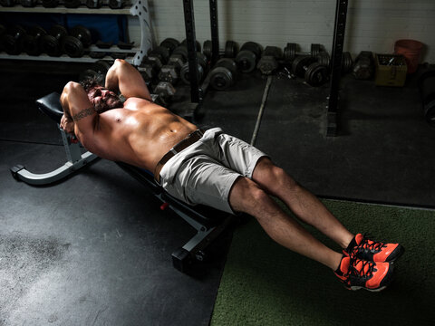A muscular man doing ab workout in gritty gym.