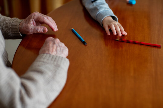 Hands of a grandfather with his grandson holding pencil