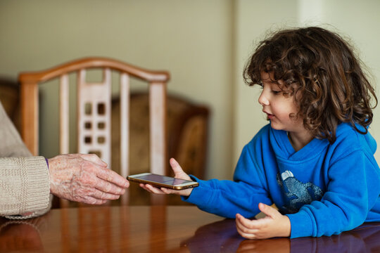 2 year old boy with his grandfather using a smartphone