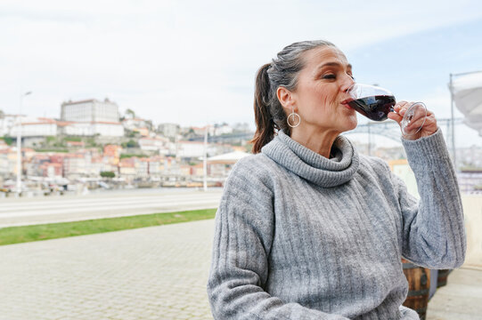Mature woman drinking a glass of wine outside