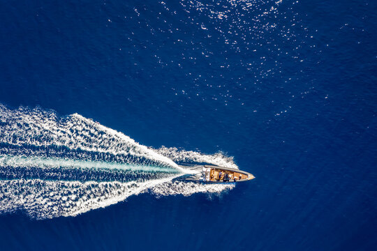 Aerial top down view of a rib motorboat traveling over blue sea