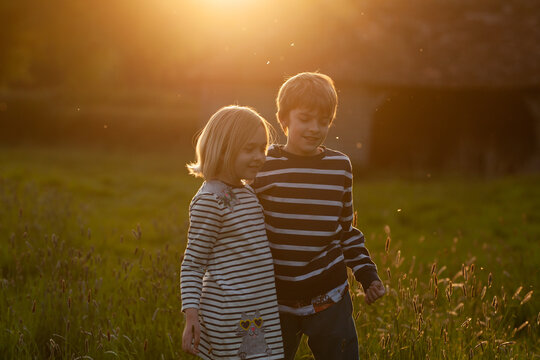 Happy siblings play together in beautiful evening light.