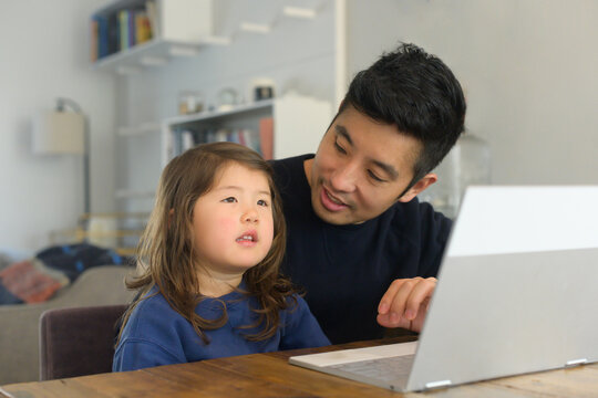 Dad on computer with daughter