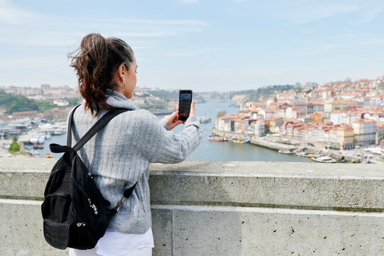 Woman taking pictures from a scenic viewpoint