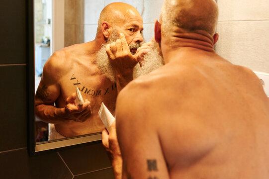 Mature man applying moisturizer in a mirror