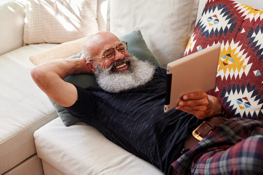 Laughing man video chatting on a tablet