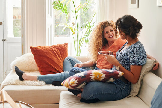 Smiling friends talking on a sofa