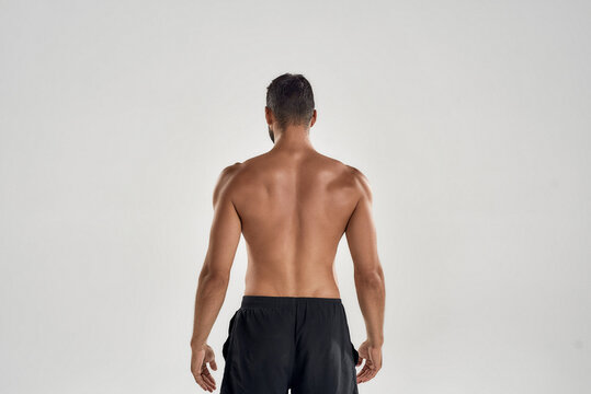 Rear view of muscular man with naked posing isolated over grey background, studio shot