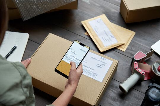 Female warehouse worker, seller, dropshipping small business owner holding phone scanning retail package postal parcel barcode on ecommerce shipping box label on smartphone using mobile app, close up.