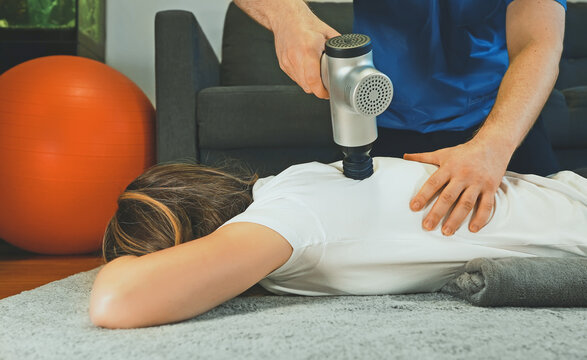 Therapist massaging woman's back with massage percussion device at her house.