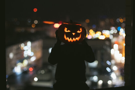 kid scares everyone with the original halloween masquerade. House party mysterious night, jack o lantern Holiday with children at home leisure entertainment. A child at the window of a big city. Scary