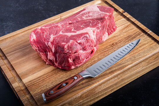 Boneless Beef Chuck Roast on a cutting board with a carving knife in the kitchen