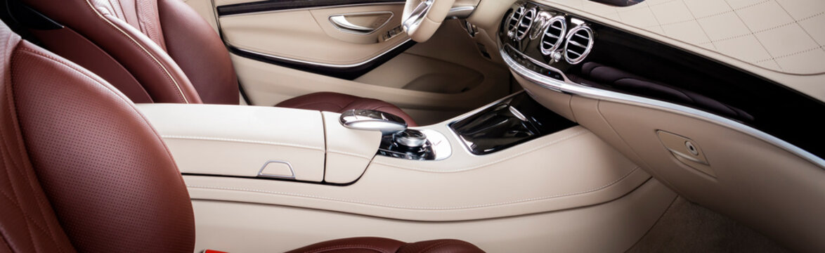 Modern luxury car Interior - steering wheel, shift lever and dashboard. Car interior luxury. Beige comfortable seats, steering wheel, dashboard, speedometer, display. Red and white perforated leather.
