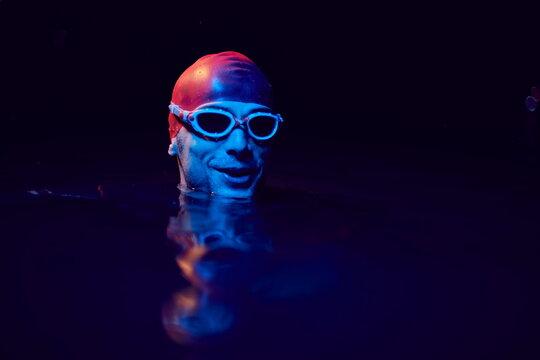 authentic triathlete swimmer having a break during hard training on night neon gel light