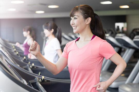 スポーツジムでランニングをする女性