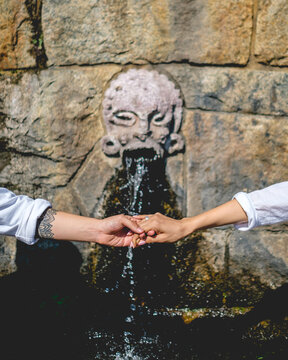 Couple with white shirts holding hands (man arm tattooed) in front of an old stone fountain of water with face on a sunny day
