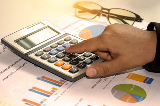 Businessmen are using a calculator to calculate expenses based on the concept of financial growth and savings for investments.