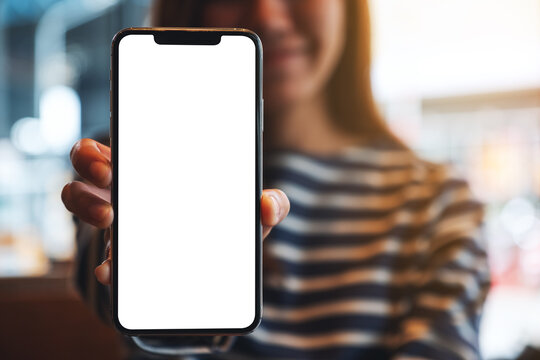 Mockup image of a beautiful asian woman holding and showing a mobile phone with blank white screen