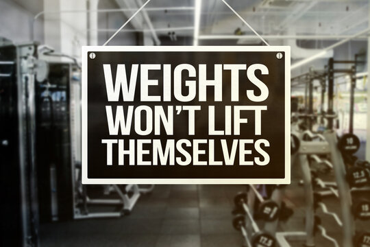 A signage with words - Weights won't Lift Themselves - in front of a gym or fitness center. Motivational quote. Yellow and black design.