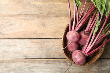Raw ripe beets in wicker bowl on wooden table, top view. Space for text