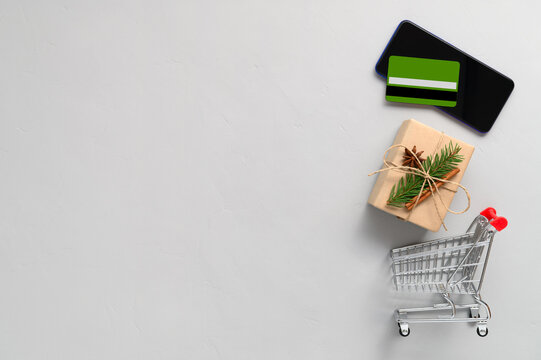 Christmas online shopping concept. Top view of smartphone, credit card, shopping trolley and gift box on light gray background. Copy space, flat lay. Winter holidays sales.